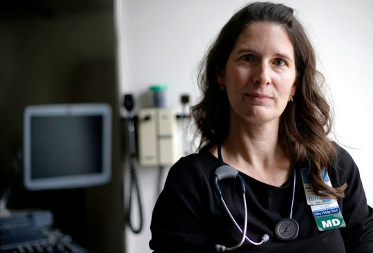 In this April 29, 2019, photo, Dr. Laura Baecher-Lind, director of women's care at Tufts Medical Center, poses for a photo in an exam room at the medical center in Boston. Lawmakers in several states say they were alarmed to learn it's still possible for medical students to do pelvic exams on anesthetized women without explicit consent, especially given evolving cultural attitudes in the #MeToo era. Doctors discuss consent forms with gynecology patients, inform them that students may participate in pelvic exams and ask for consent, said Baecher-Lind. (AP Photo/Steven Senne)