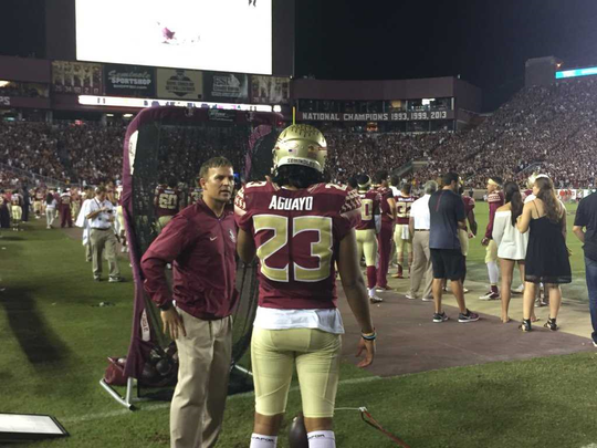Trevor Moawad speaks to Florida State kicker Ricky Aguayo on the sidelines during a Seminoles game.