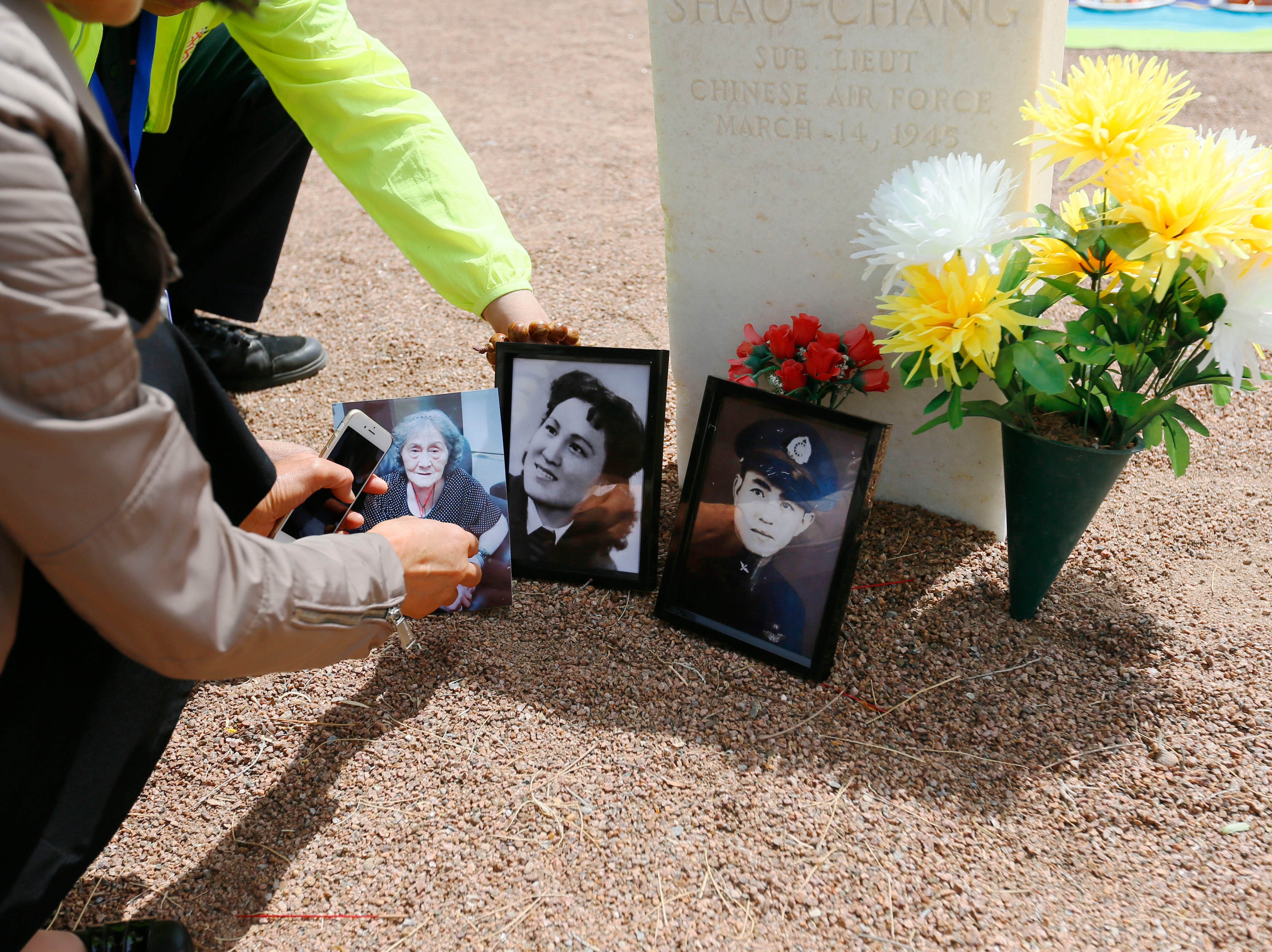 Feng Zhong shows photos of his great uncle Van Shao-Chang and his mother next to Van Shao-Chang's burial site Monday, May 13, at Fort Bliss National Cemetery. The Hunan LongYue Peace Charity Development Center brought family members to El Paso to pay a special remembrance to their relatives who are amongst the 52 Chinese pilots who died in the U.S. during flight training in World War II.