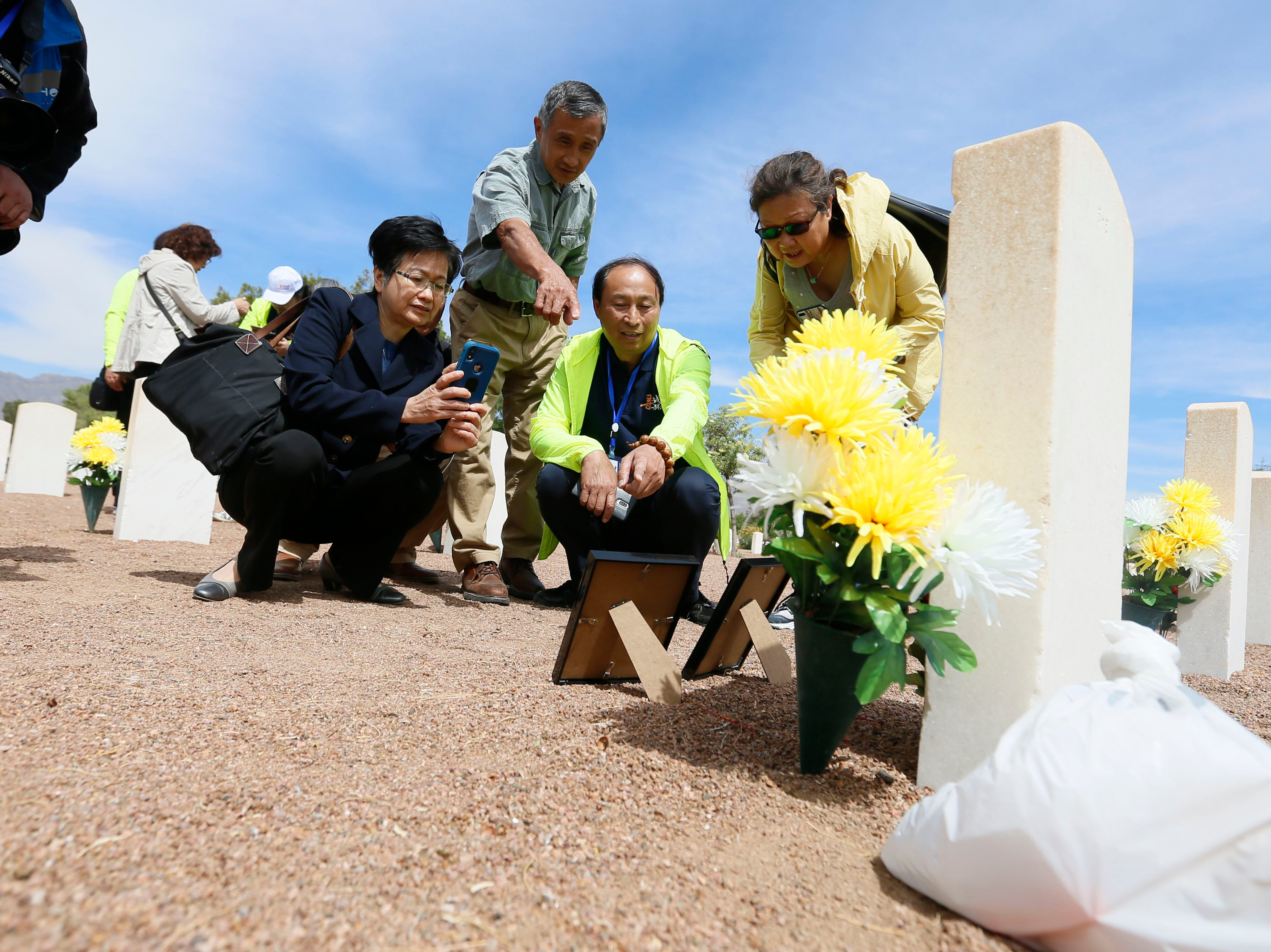Anita Shing takes a photo on her phone, left, as Feng Zhong, center, shows her a photo of his great uncle Van Shao-Chang next to his burial site Monday, May 13, at Fort Bliss National Cemetery. The Hunan LongYue Peace Charity Development Center brought family members to El Paso to pay a special remembrance to their relatives who are amongst the 52 Chinese pilots who died in the U.S. during flight training in World War II.