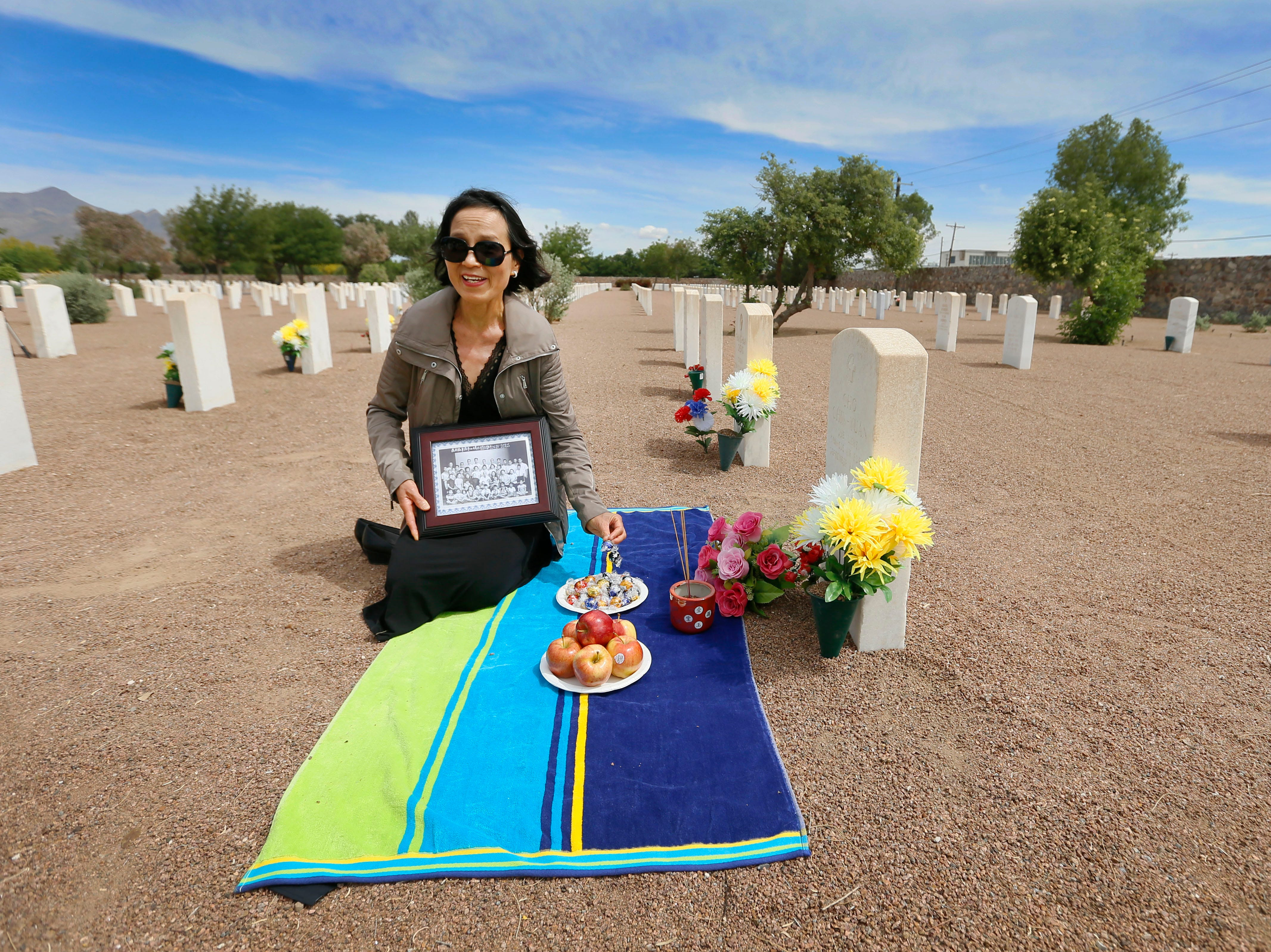Jianwu Li takes apples, chocolates and incense to her great uncle Cho Chin-Yuan's burial site Monday, May 13, at Fort Bliss National Cemetery. Jianwu Li came from Sacramento, California after the Hunan LongYue Peace Charity Development Center informed her that her great uncle was buried there. She brought a family photo with her. She said he had already passed away by the time the family photo was taken. The Hunan LongYue Peace Charity Development Center brought family members to El Paso to pay a special remembrance to their relatives who are amongst the 52 Chinese pilots who died in the U.S. during flight training in World War II.
