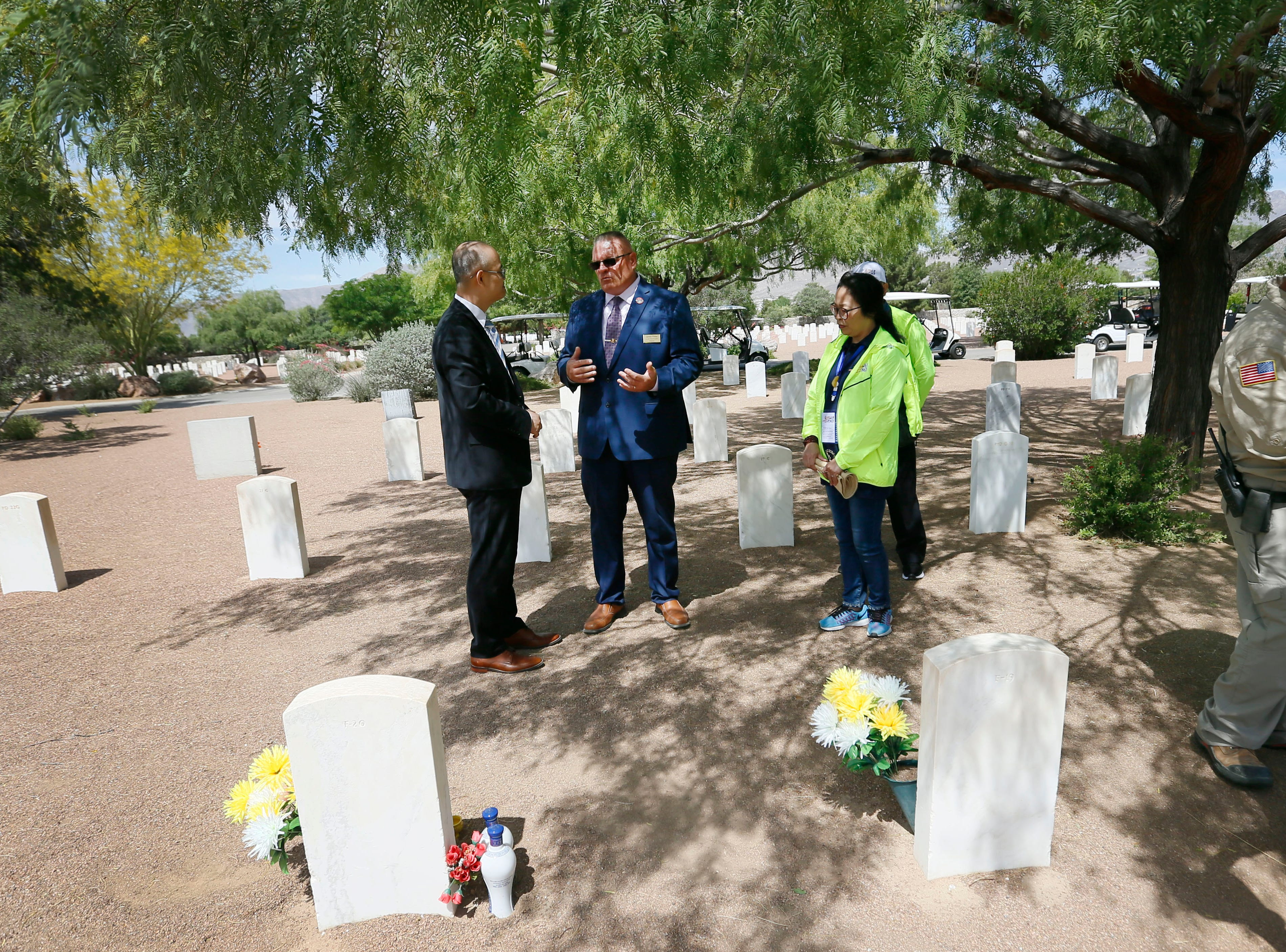 Fort Bliss National Cemetery Director James Porter, center, visits grave sites with families brought to El Paso by the Hunan LongYue Peace Charity Development Center Monday, May 13, to pay a special remembrance to their relatives who are amongst the 52 Chinese pilots who died in the U.S. during flight training in World War II.