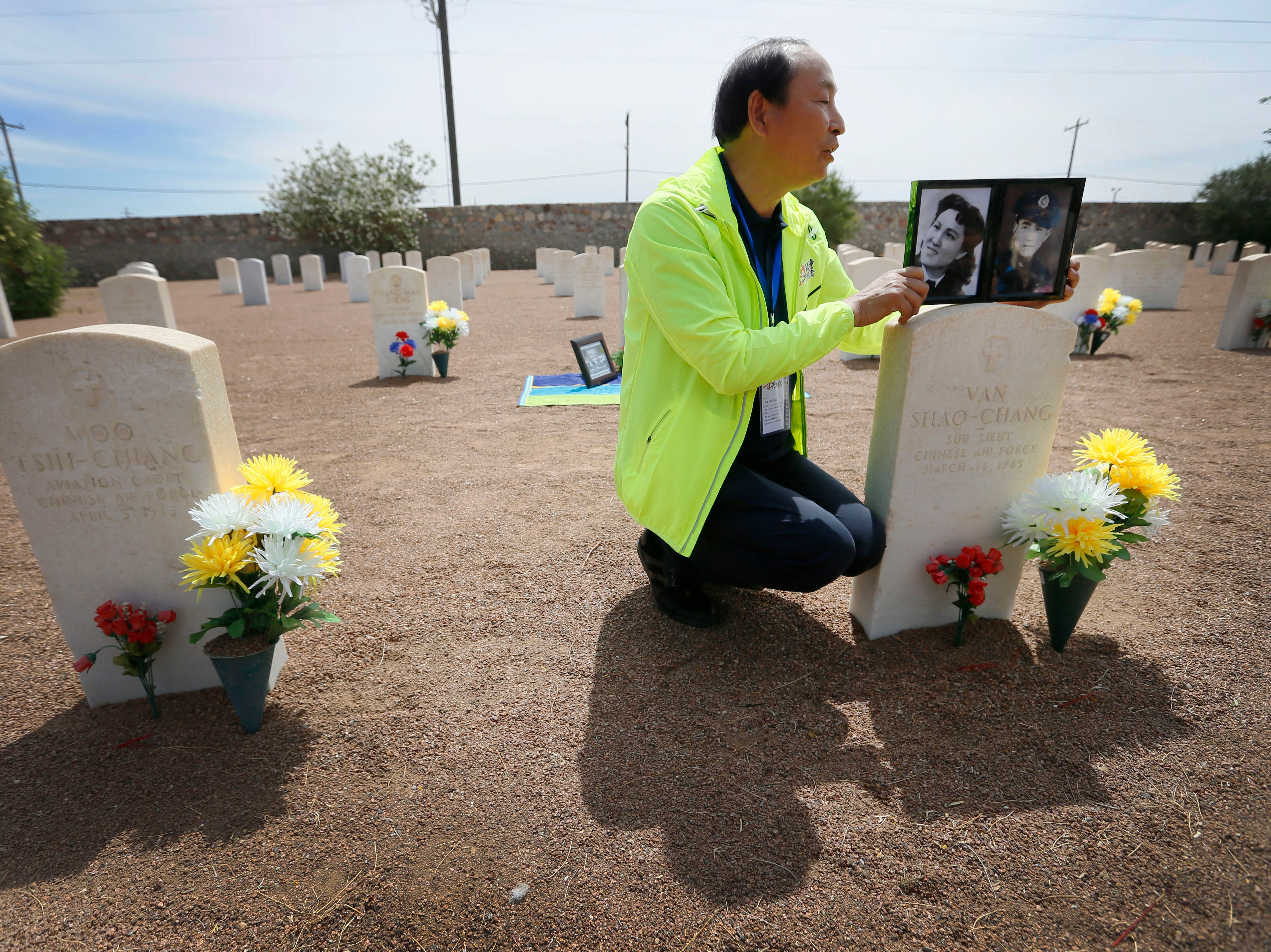 Feng Zhong shows photos of his uncle Van Shao-Chang and his mother next to Van Shao-Chang's burial site Monday, May 13, at Fort Bliss National Cemetery. The Hunan LongYue Peace Charity Development Center brought family members to El Paso to pay a special remembrance to their relatives who are amongst the 52 Chinese pilots who died in the U.S. during flight training in World War II.
