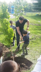 Chris Laferty, kindergarten teacher, Ellison School, is assisted by an Ellison student during the school's Arbor Day celebration, which featured the planting of a red maple tree donated by the Vineland Environmental Commission.