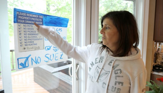 Lynne Munroe at her Valley Cottage home with a sign opposing Suez Water's plan to move into Tilcon's old offices in West Nyack across from her backyard May 13, 2019.