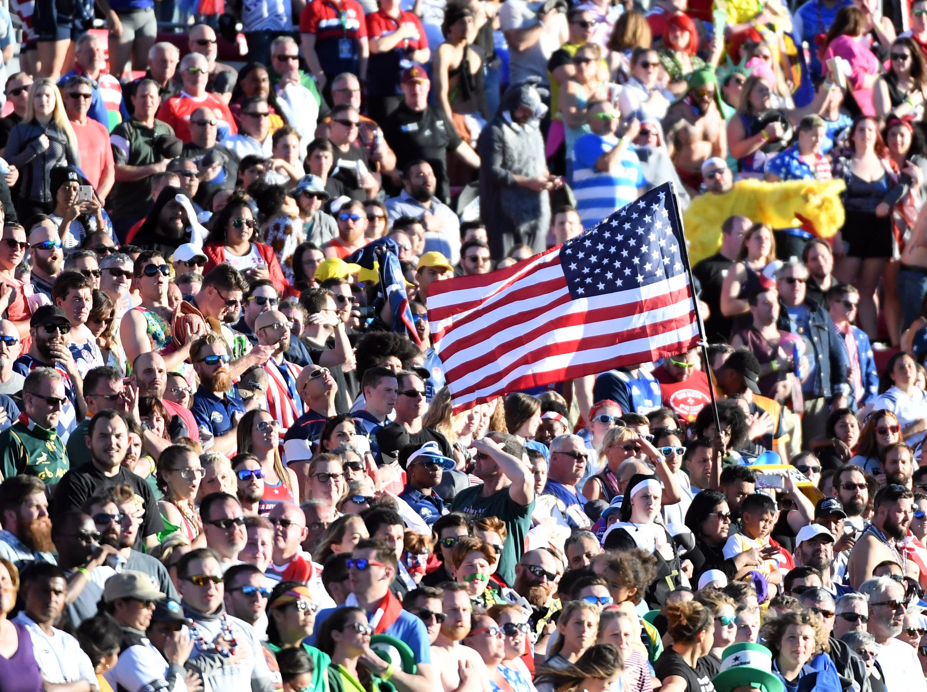 A fan waves an American flag as the national anthem of the United States is performed before the Cup Final match between the United States and Samoa during the USA Sevens Rugby tournament at Sam Boyd Stadium on March 3, 2019 in Las Vegas, Nevada. The United States won 27-0. A. Jon Prusmack revived the USA Sevens, moved it to Las Vegas and grew it to one of the most popular tour stops on the international calendar.
