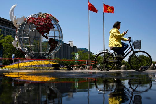 A woman rides a bicycle past a globe structure on display outside a bank in Beijing, Monday, May 6, 2019.