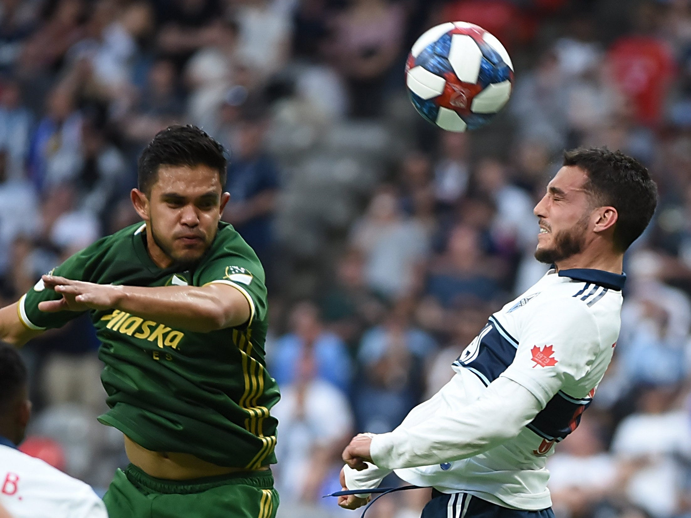 May 10: Vancouver Whitecaps midfielder Russell Teibert (31) goes up for a header against Portland Timbers midfielder Andres Flores (14) during the first half at BC Place. Vancouver won the game, 1-0.