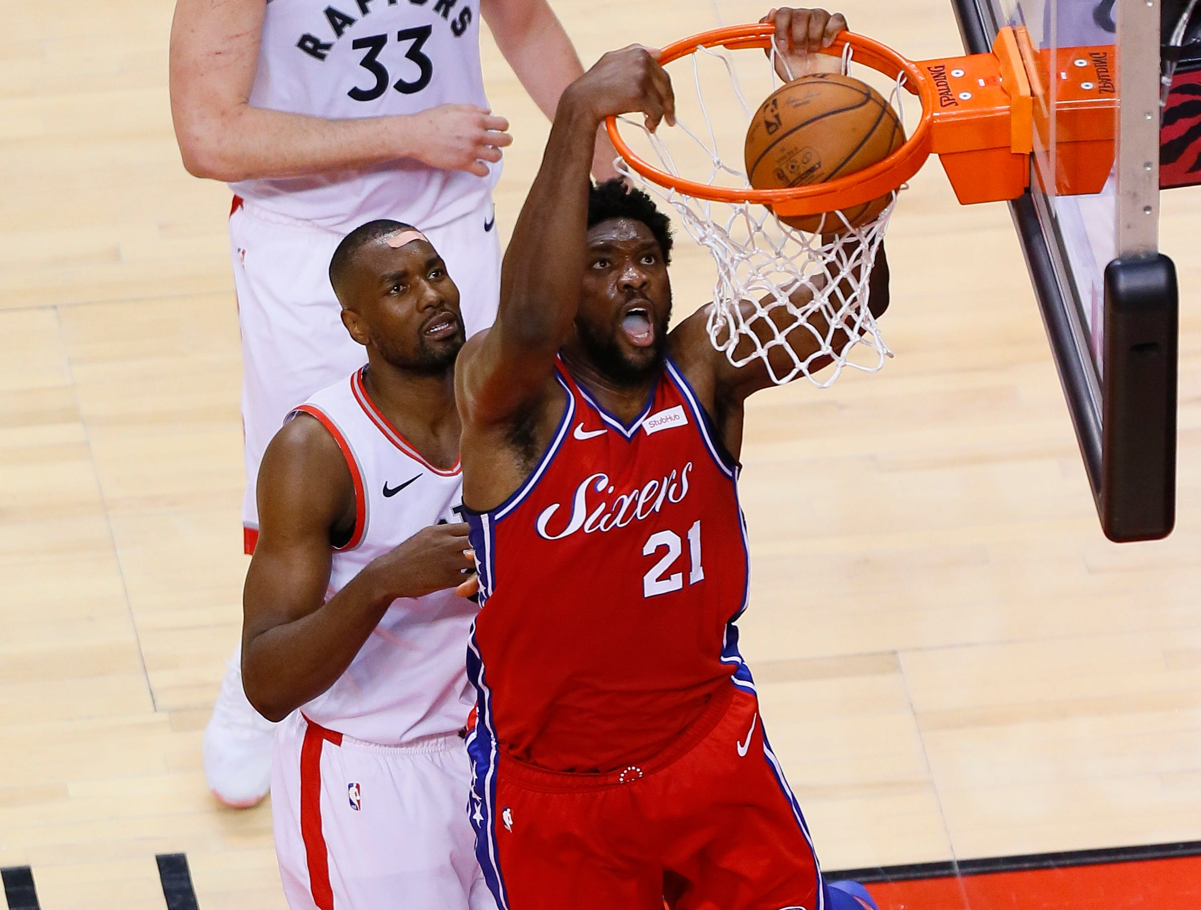 May 12: Sixers center Joel Embiid (21) throws down the two-handed slam against Raptors defender Serge Ibaka (9) during Game 7.