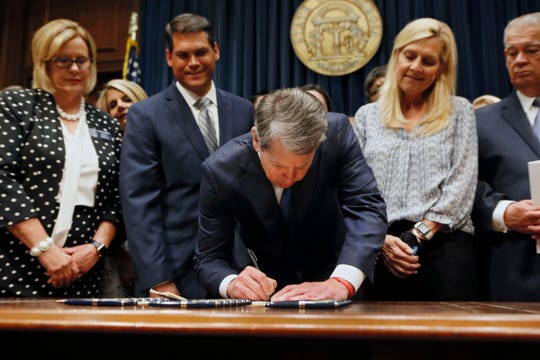 Georgia's Republican Gov. Brian Kemp signs legislation banning abortions once a fetal heartbeat can be detected in Atlanta on May 7, 2019.