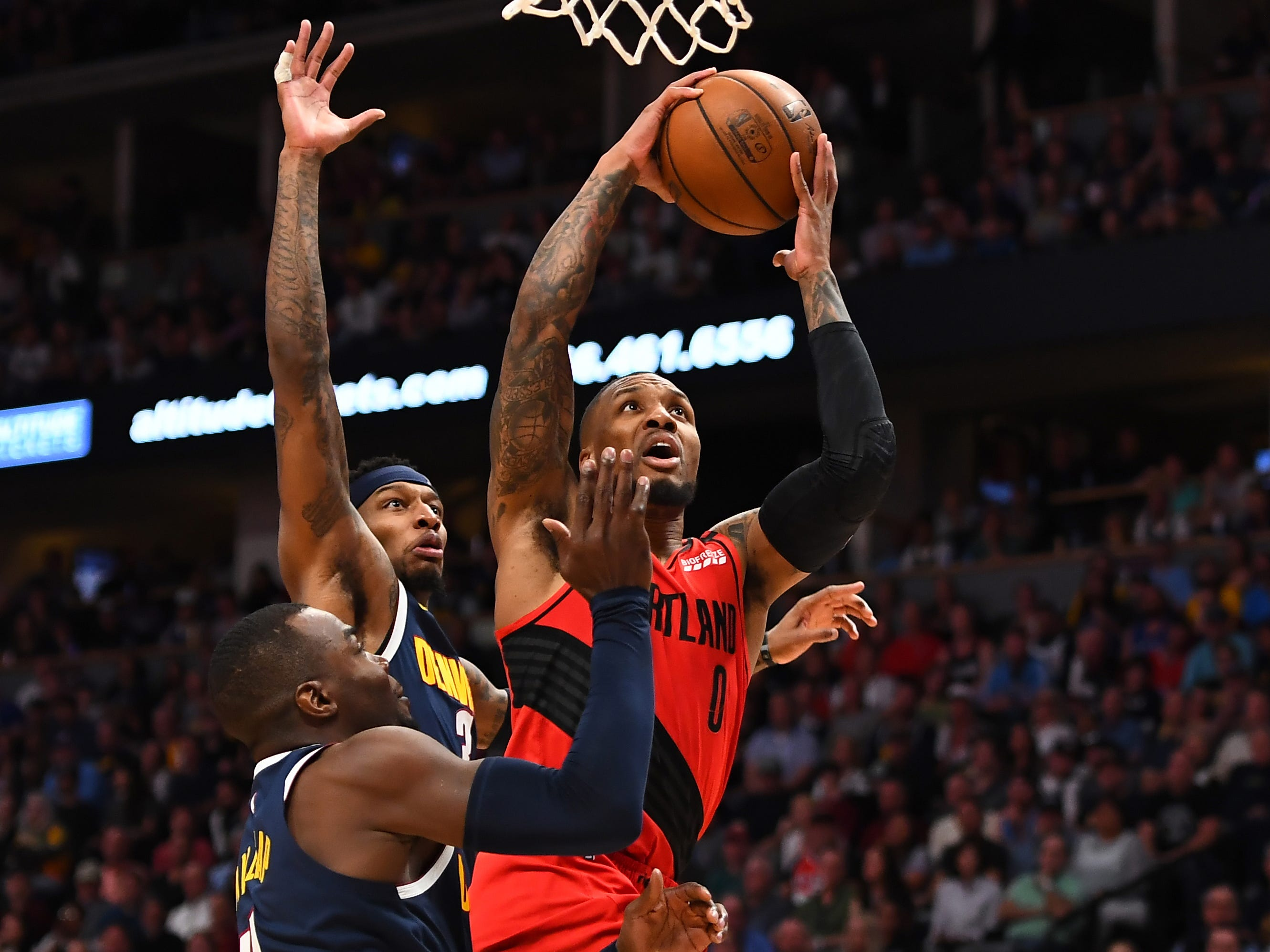 May 12: Blazers guard Damian Lillard (0) drives to the bucket against Nuggets defenders Paul Millsap (4) and Torrey Craig (3) during Game 7.