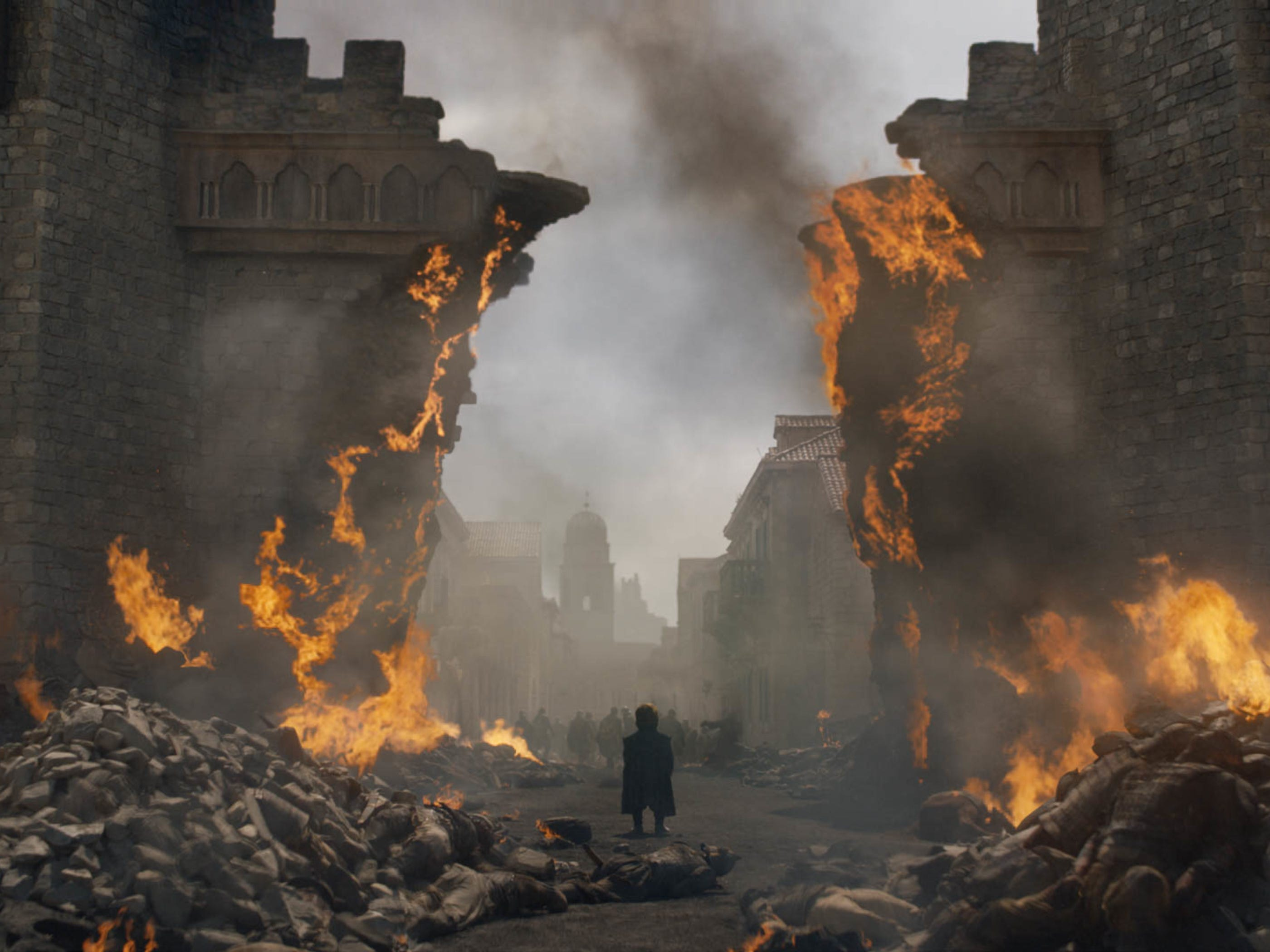 Tyrion Lannister (Peter Dinklage) stands amid the burning ruins of King's Landing.