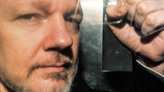 Julian Assange gestures from the window of a prison van in London.