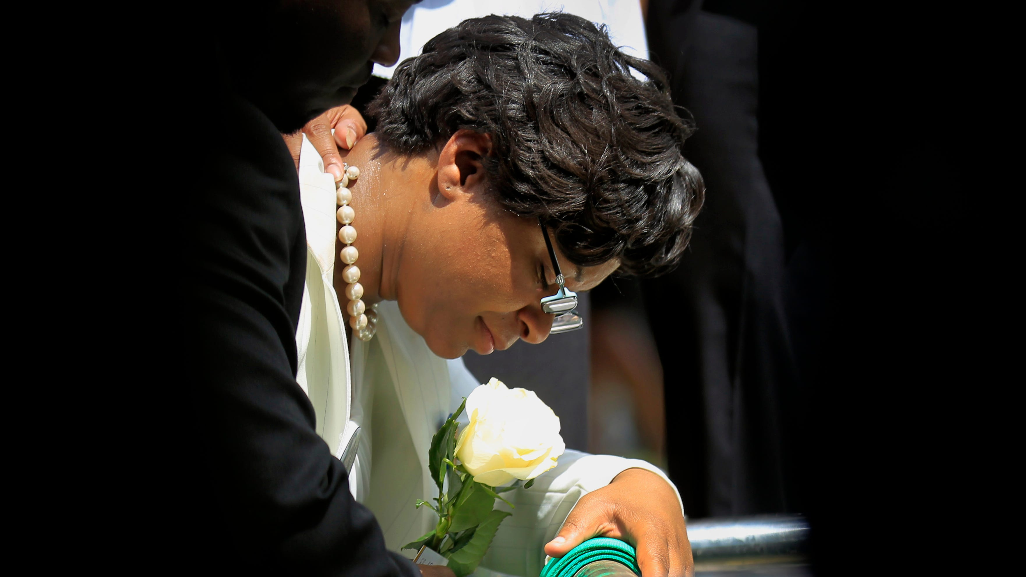 Sandra Bland's sister Sharon Cooper kneels at Bland's burial site at the Mt. Glenwood Memorial Gardens West cemetery on Saturday, July 25, 2015, in Willow Springs, Ill.