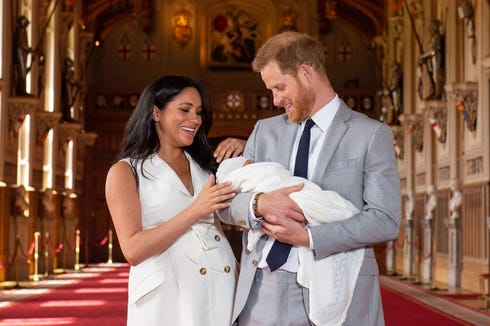 Prince Harry and Duchess Meghan of Sussex pose with their newborn son at Windsor Castle, two days after his birth.