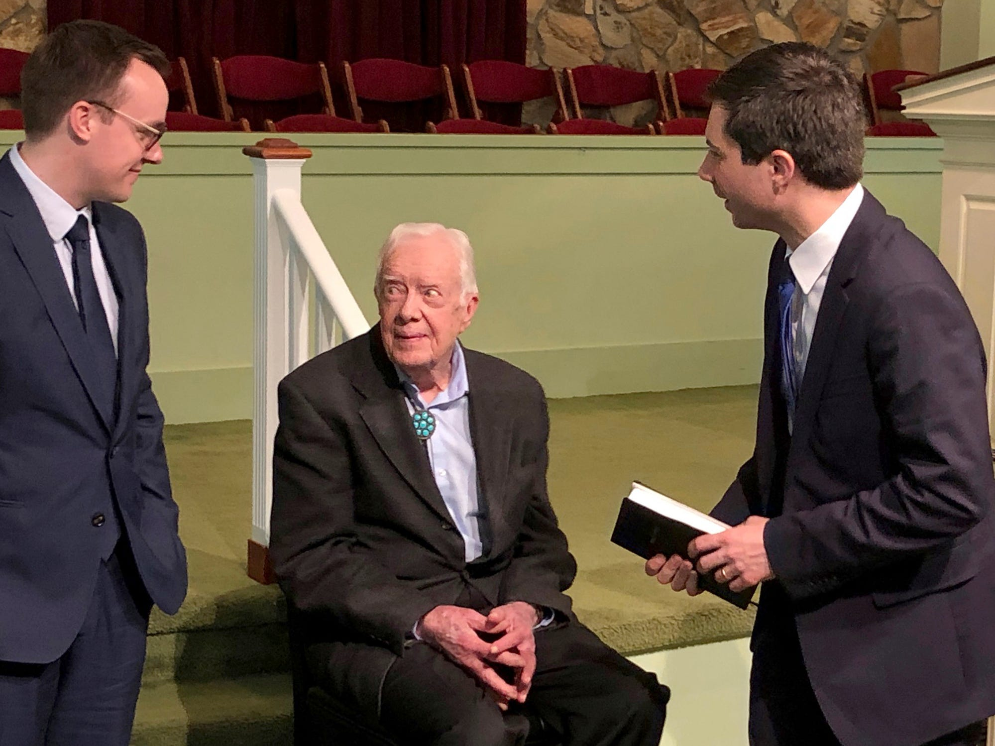 Democratic presidential candidate Pete Buttigieg, right, and his husband, Chasten Glezman, left, speak with former President Jimmy Carter at former President Jimmy Carter's Sunday school class in Plains, Ga. Sunday, May 5, 2019.