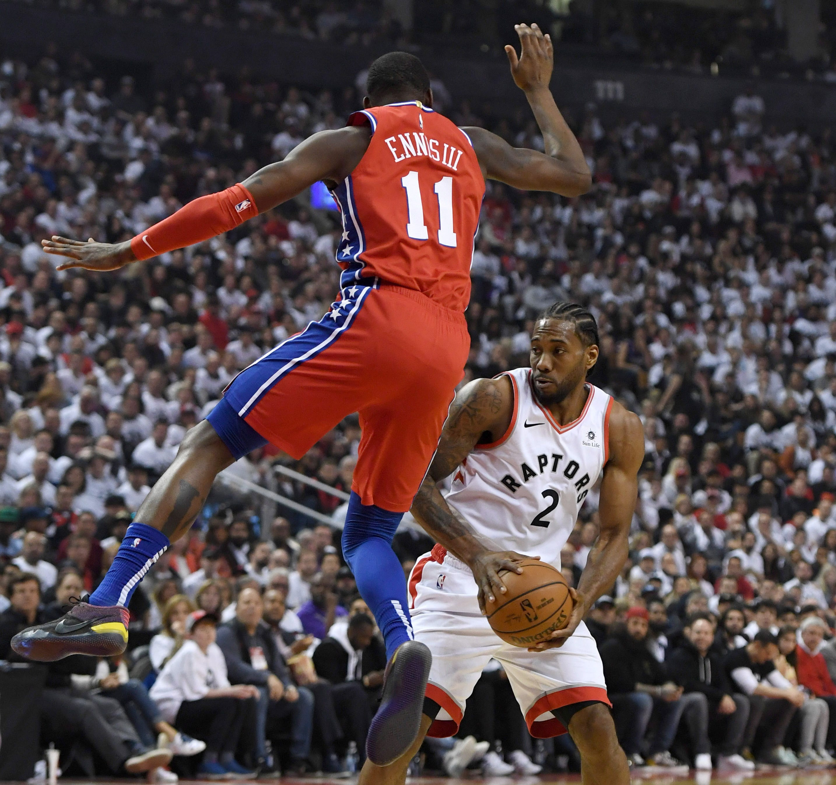 May 12: Raptors forward Kawhi Leonard (2) gets 76ers defender James Ennis III (11) off his feet with a ball fake during Game 7 in Toronto.