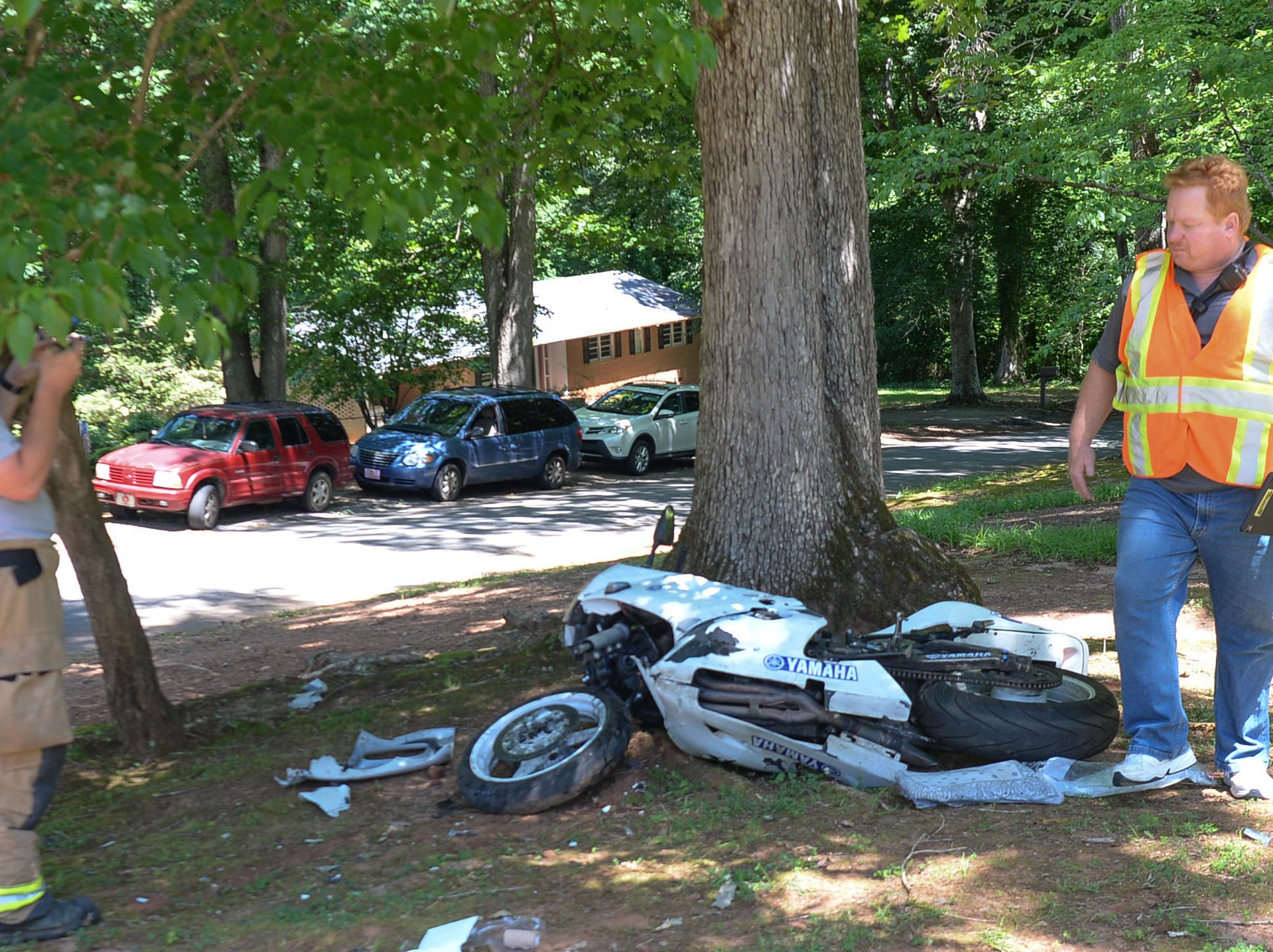 Emergency workers look over a young woman who crashed her motorcycle into a tree in Anderson Tuesday. Homeland Park firemen and Medshore also responded to the accident.