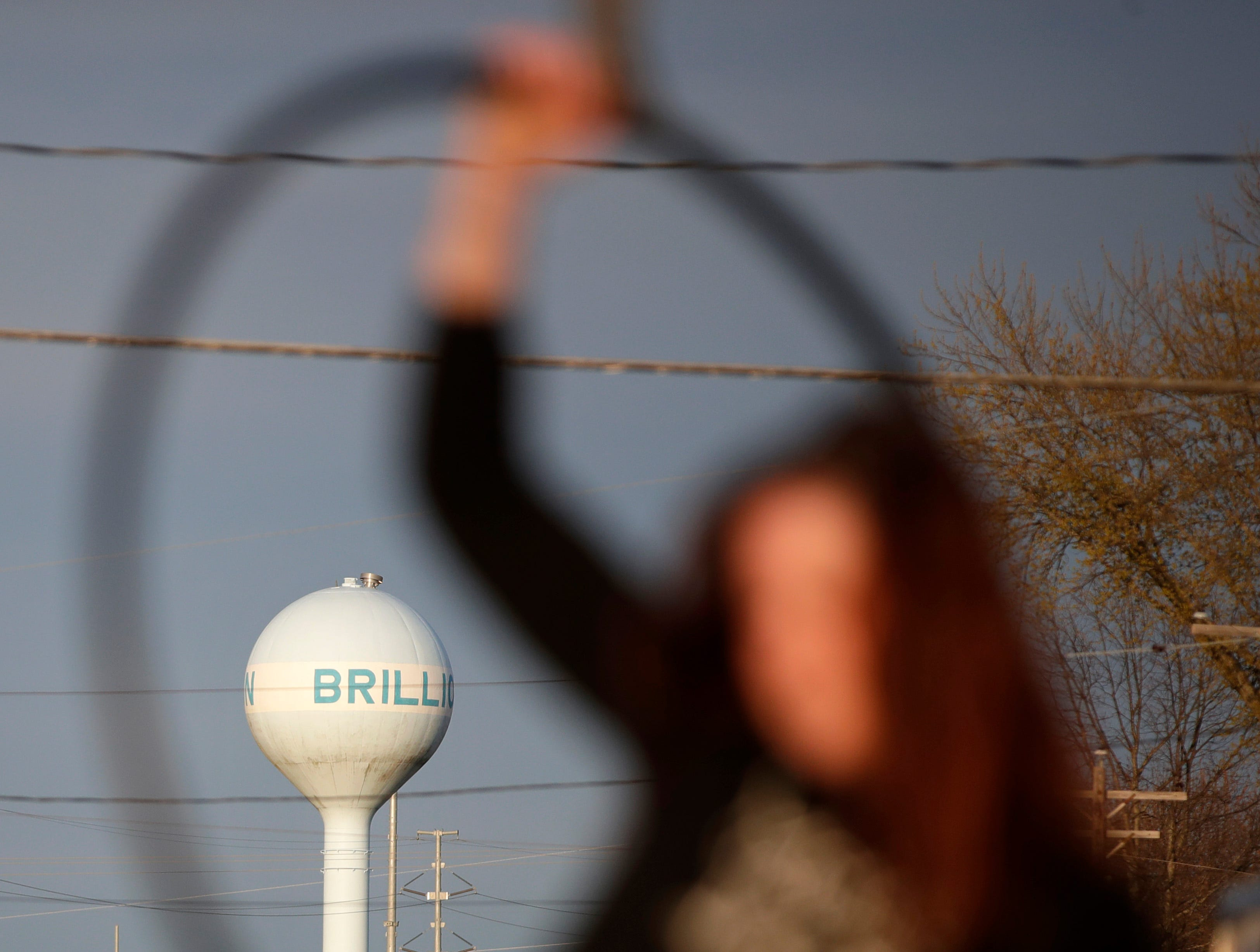 The Brillion water tower can be seen through the hoop that Amy Hart, with Aerial Dance, perform with during the first Bazaar After Dark of the year Saturday, May 11, 2019, in Brillion, Wis. 