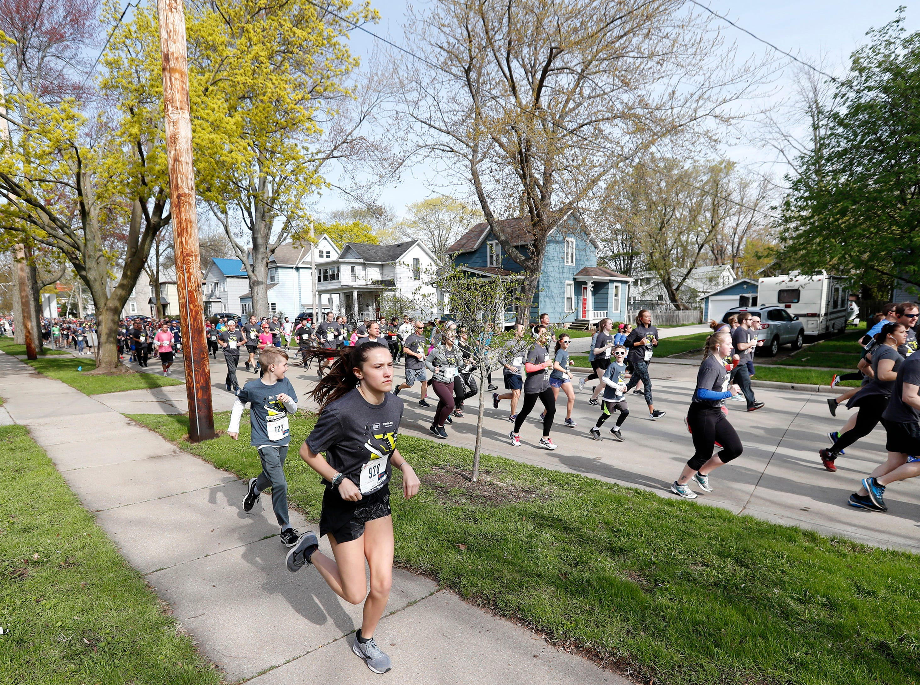Runners take to the sidewalk just past the starting line of the Sole Burner 5K Walk-Run Saturday, May 11, 2019, in Appleton, Wis. 