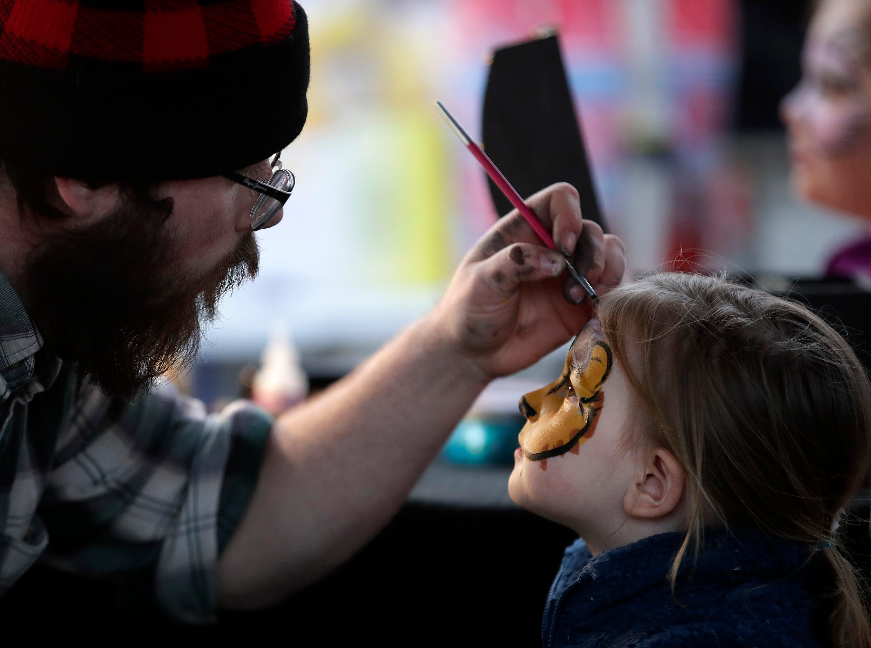 Tommy Mlodzik, with Mischief & Magic, paints Hope Choronzy's, 3, of Sherwood, face during Bazaar After Dark Saturday, May 11, 2019, in Brillion, Wis. 