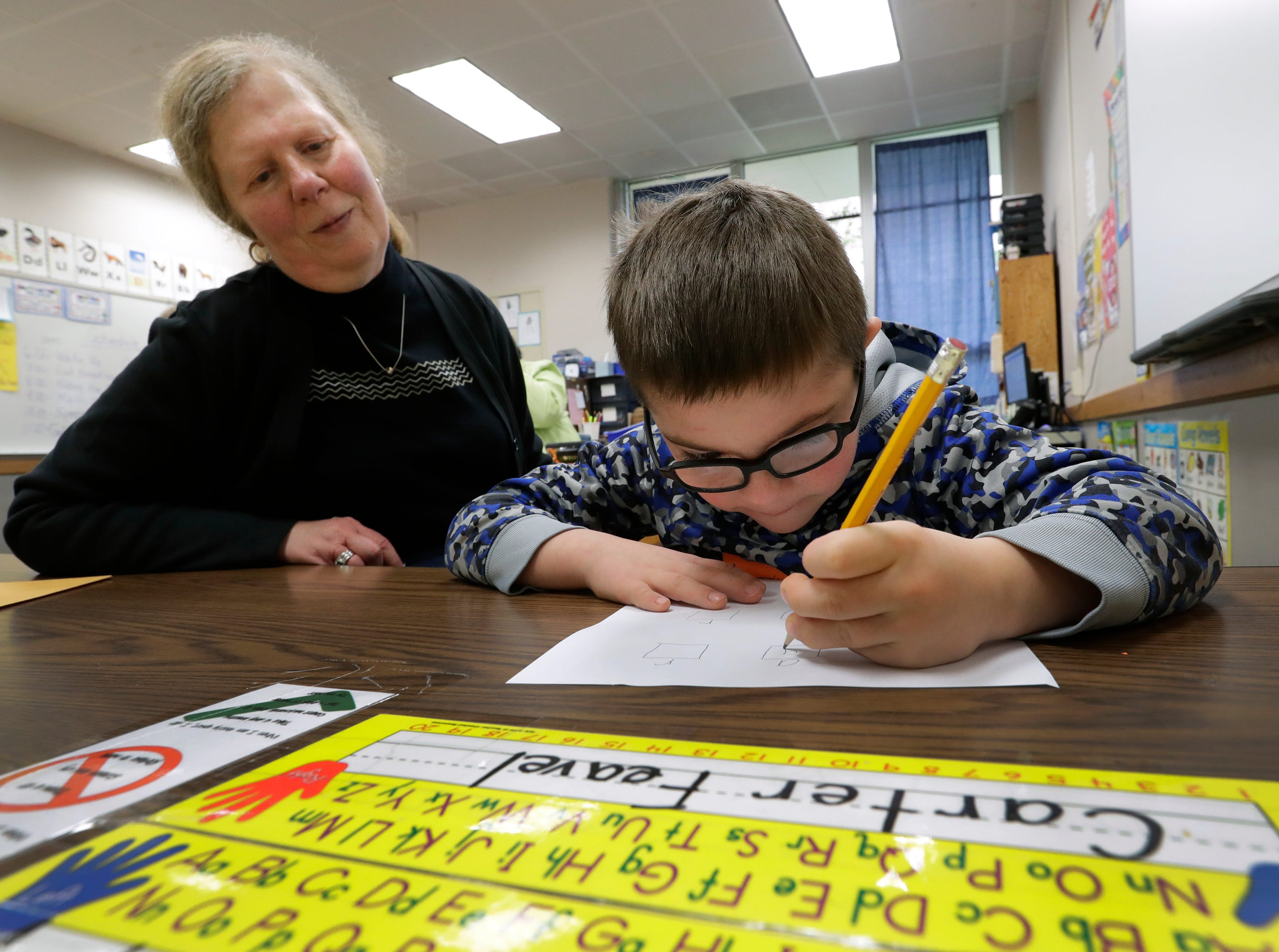 Paraprofessional Diane Conrad helps Carter Feavel work on writing letters of the alphabet during his intellectual disabilities cross categorical special education class Thursday, May 9, 2019, at Huntley Elementary School in Appleton, Wis. 