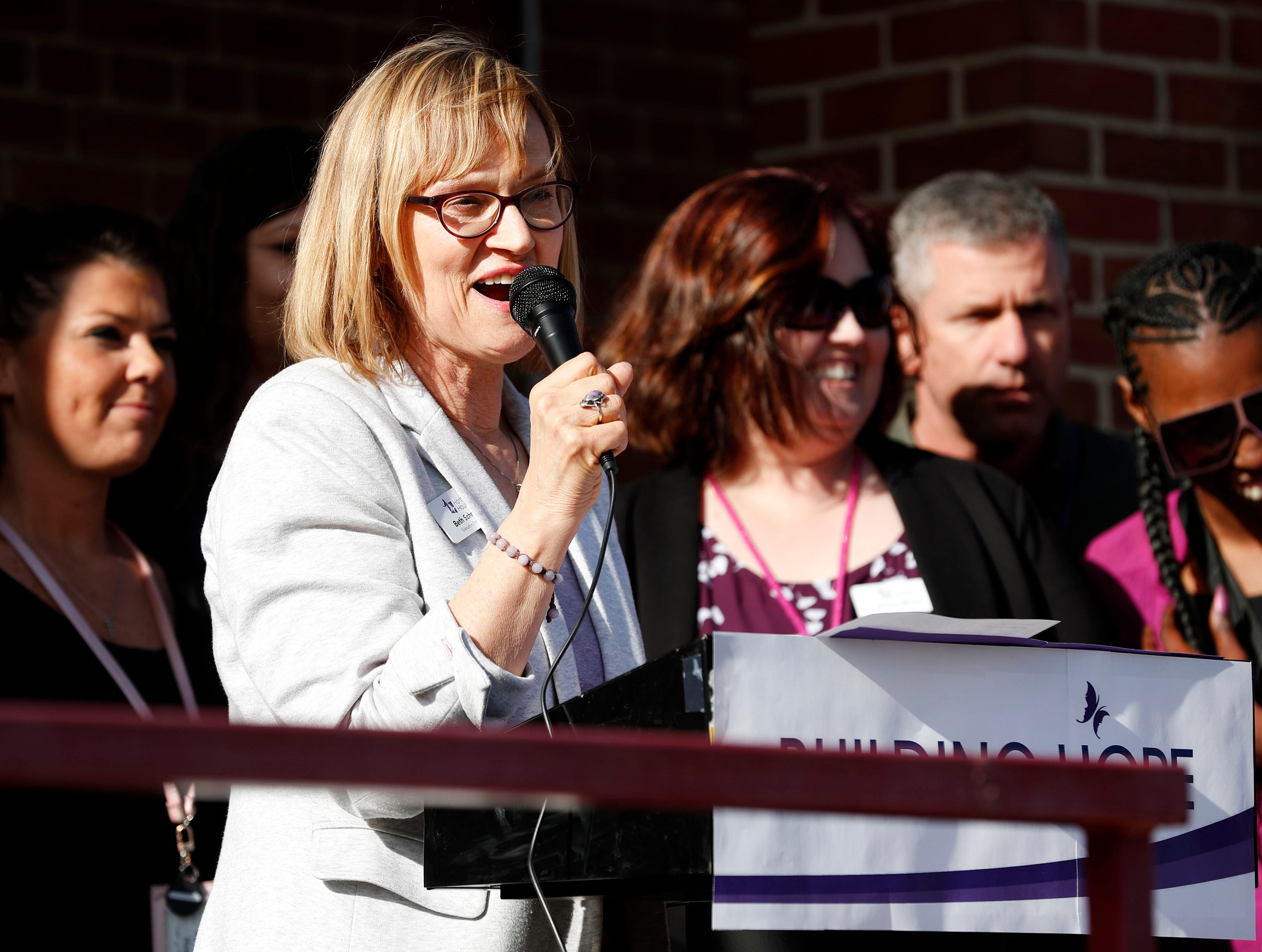 Beth Schnorr, executive director of Harbor House Domestic Abuse Programs, speaks to a crowd gathered at the ribbon cutting and open house for Harbor House's updated facilities Tuesday, May 7, 2019, in Oshkosh, Wis. 