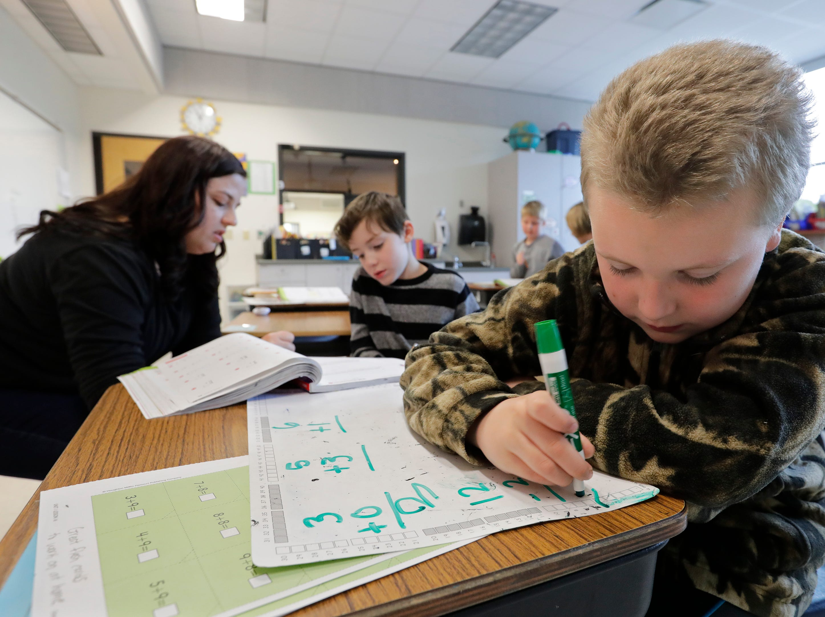 Hunter Doering, right, takes a math test as autism teacher Ashley Hermans works with Gavin Goerl Thursday, May 9, 2019, at Huntley Elementary School in Appleton, Wis. 