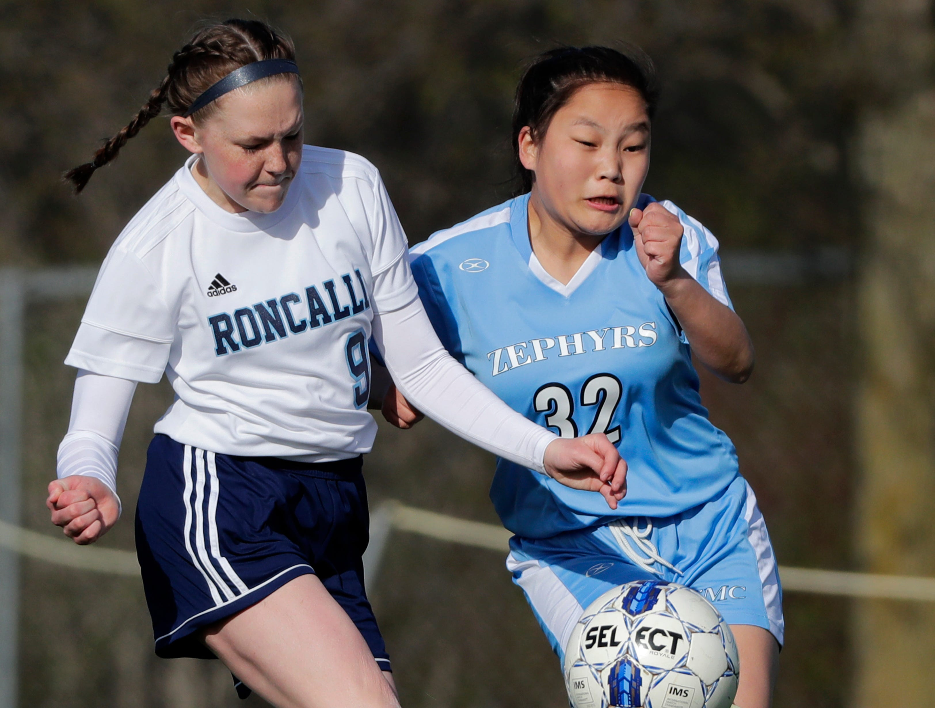 St. Mary Catholic High School's Agii Kerwin (32) takes a shot on goal against Roncalli High School's Natalie Putman (9) during their girls soccer game Tuesday, May 7, 2019, in Fox Crossing, Wis. 