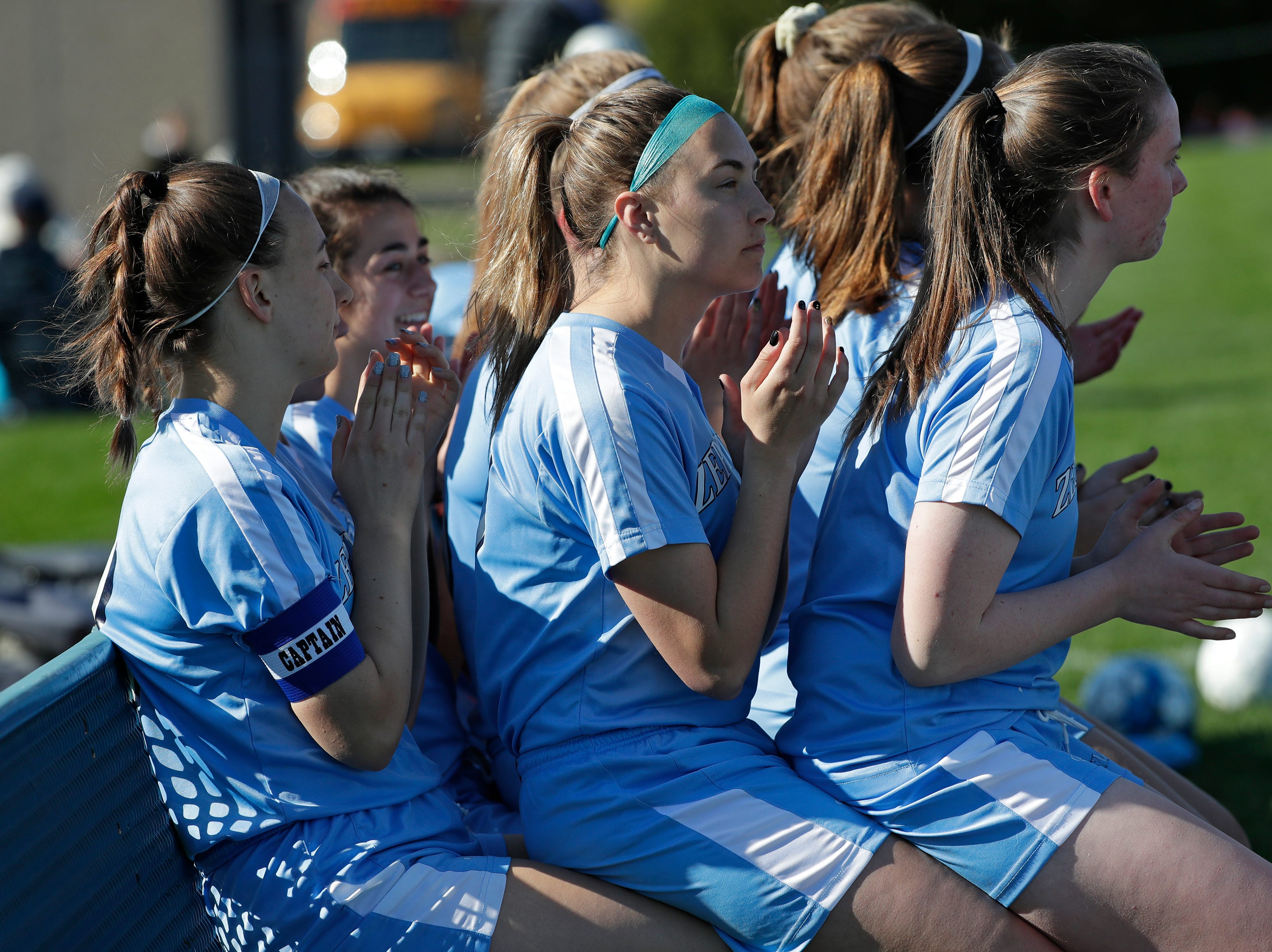 St. Mary Catholic High School's Sydney Andersen, left, Ashley Trebatoski and Ruth Meier sit on each others' laps as they are announced against Roncalli High School during their girls soccer game Tuesday, May 7, 2019, in Fox Crossing, Wis. 