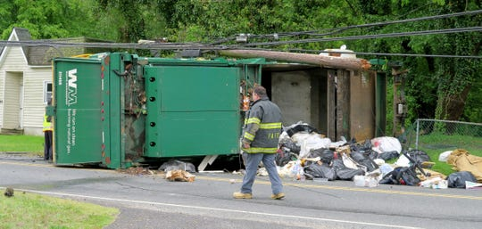 A Waste Management garbage truck overturned on West Farms Road at Casino Drive in Howell Township Tuesday morning, May 14, 2019.  At least two people were injured in the collision that spilled garbage on the roadway and cracked a utility pole.