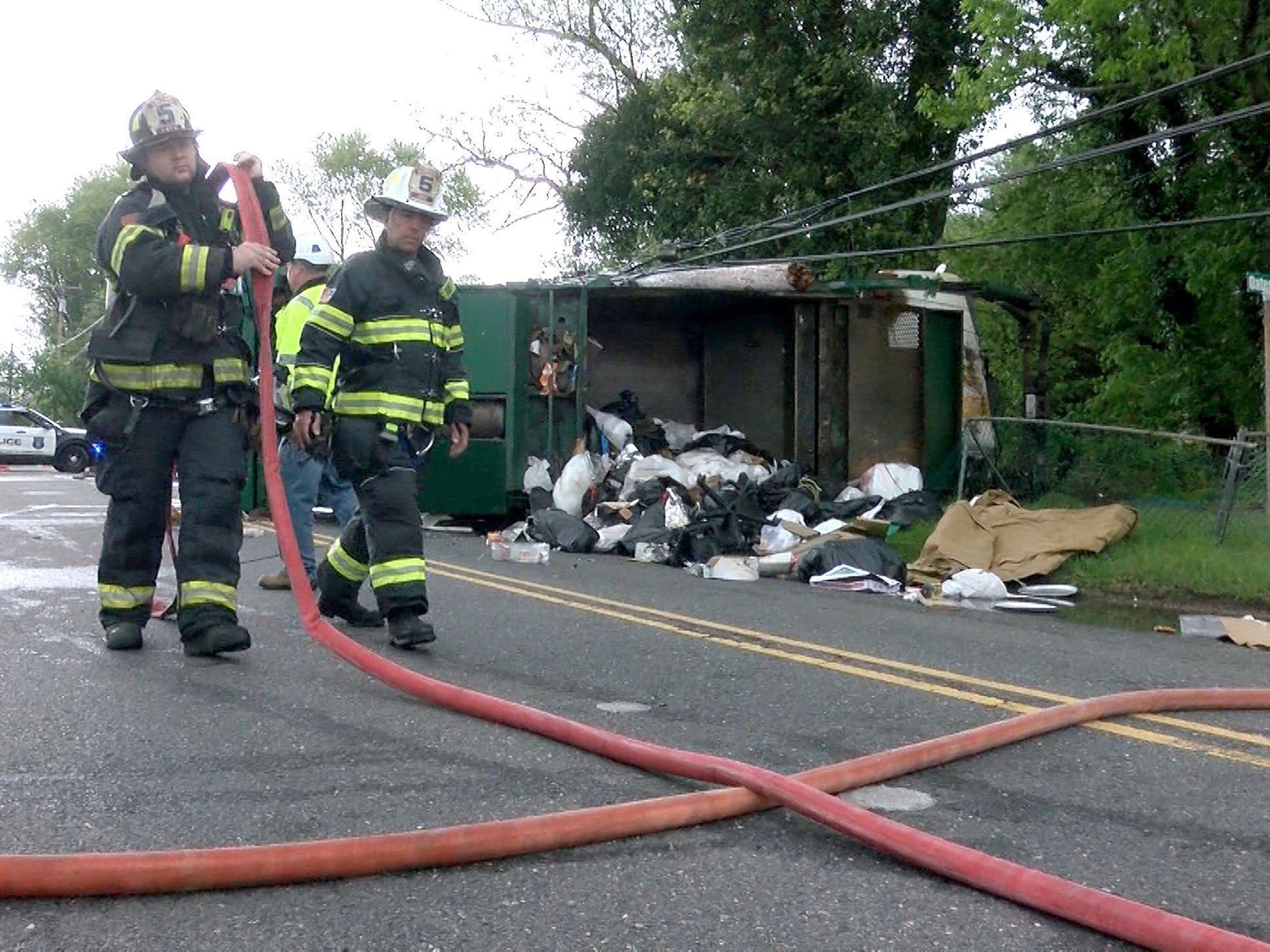 Howell Township firefighters pick up hose after a Waste Management garbage truck overturned on West Farms Road at Casino Drive in the Township Tuesday morning, May 14, 2019.  At least two people were injured in the collison that spilled garbage on the roadway and cracked a poer pole.