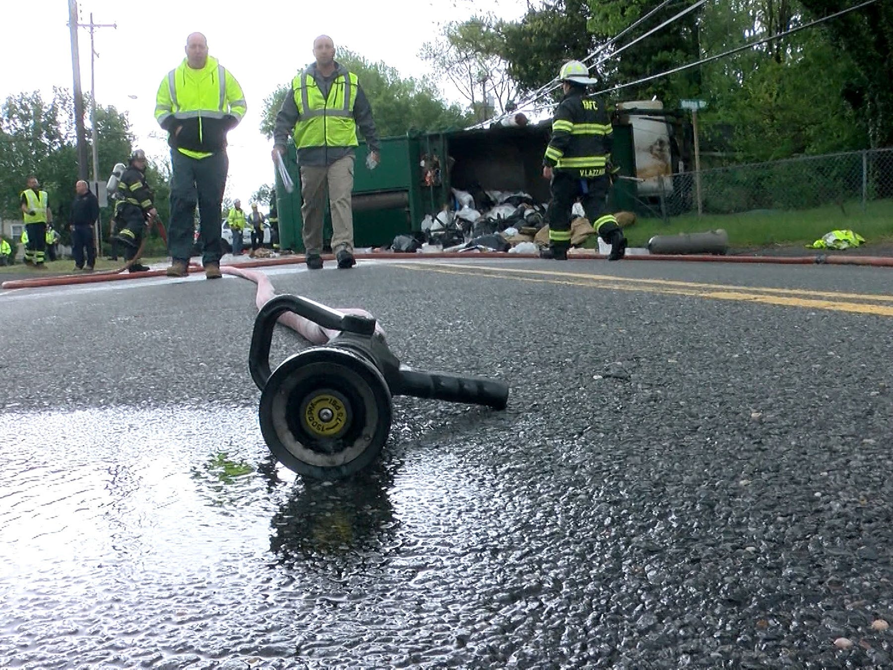 A hose drains in the street near a Waste Management garbage truck that overturned on West Farms Road at Casino Drive in Howell Township Tuesday morning, May 14, 2019.  At least two people were injured in the collison that spilled garbage on the roadway and cracked a poer pole.