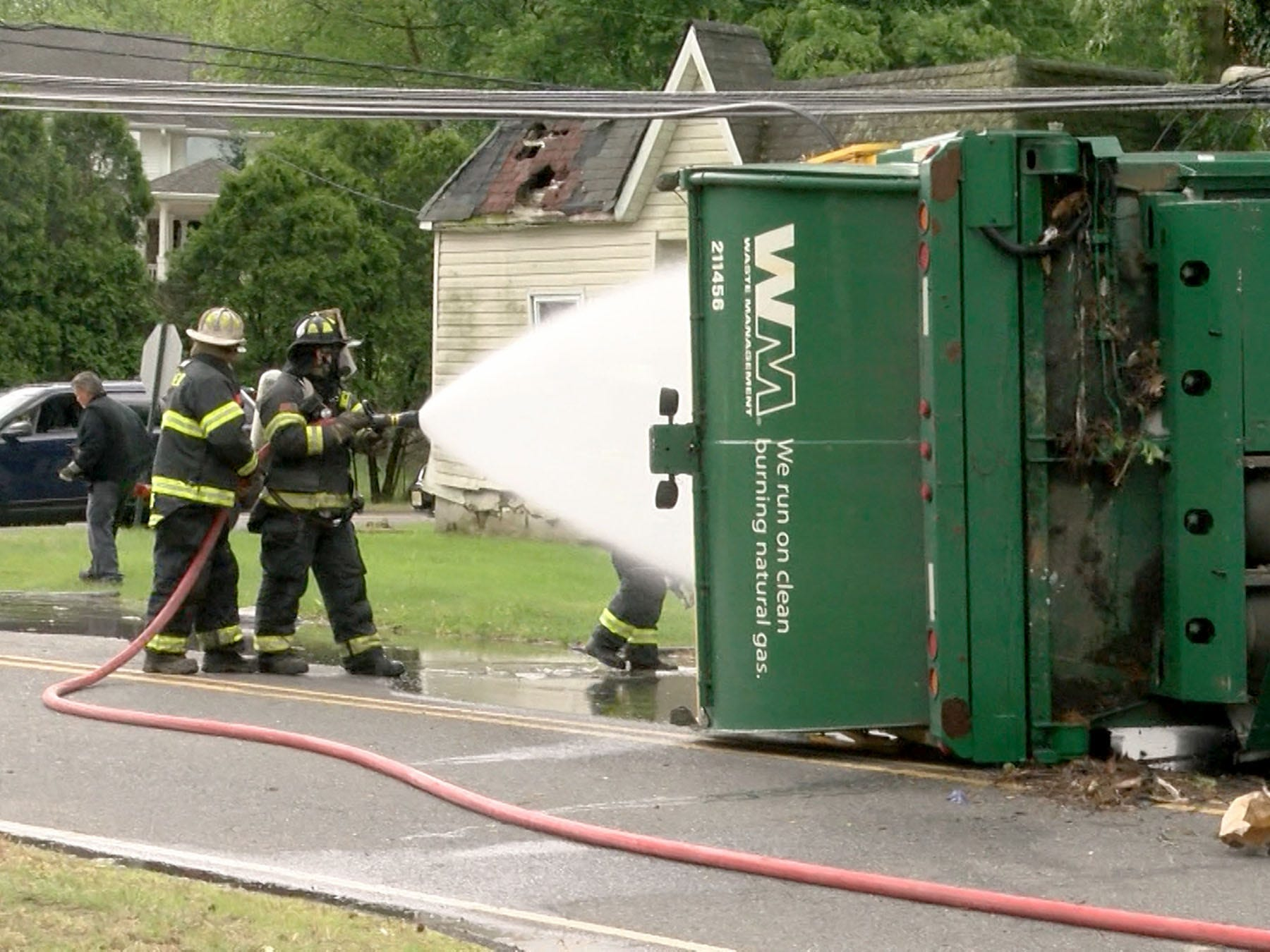 Howell Township firefighters keep an overtuned Waste Management garbage truck cool on West Farms Road at Casino Drive in the Township Tuesday morning, May 14, 2019.  At least two people were injured in the collison that spilled garbage on the roadway and cracked a poer pole.