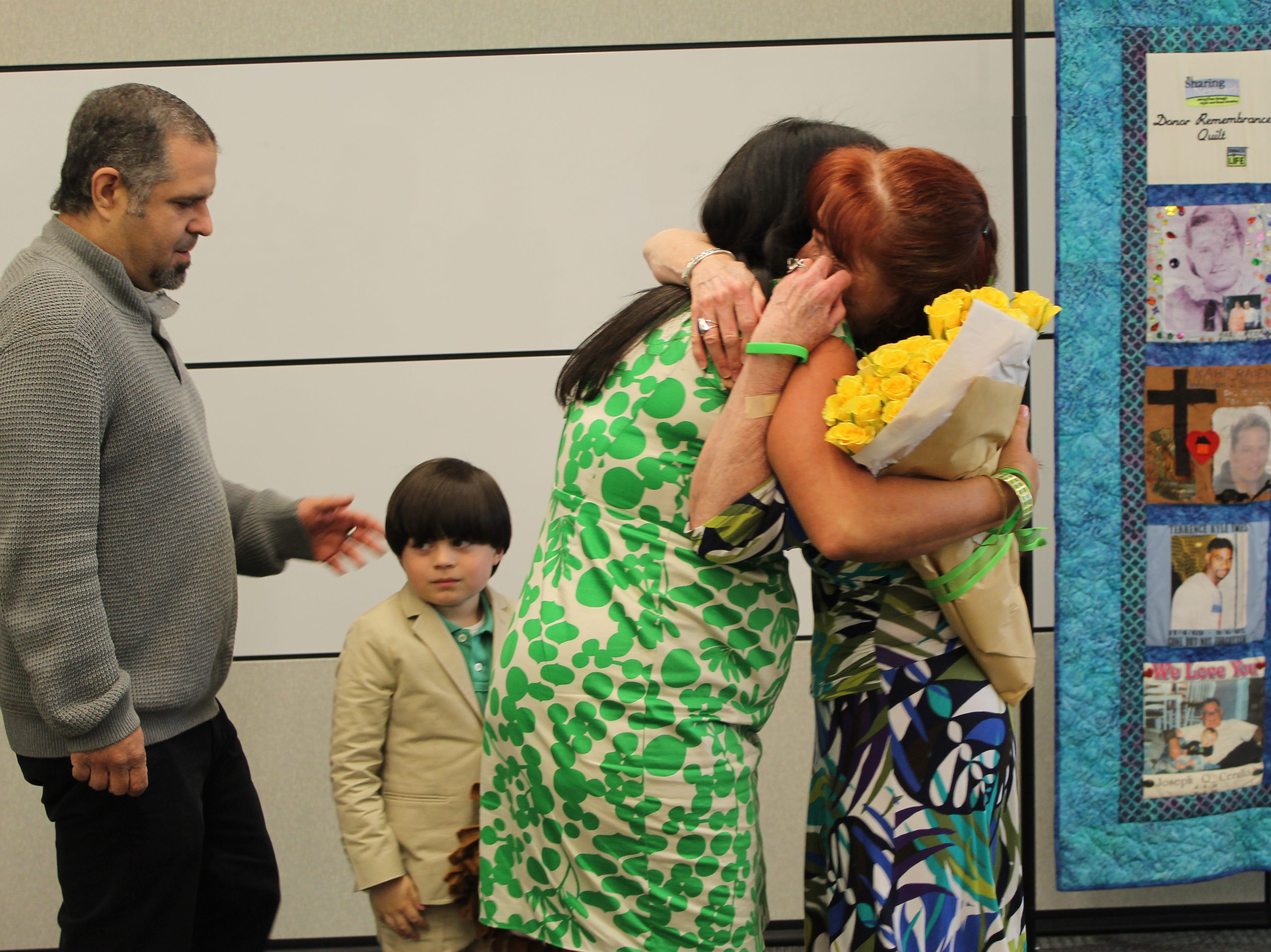 Dorothea Duffy (right) embraces Susan Callari Diamond upon their first meeting in 2016 as Michael Diamond (far left) and Jake Diamond look on.