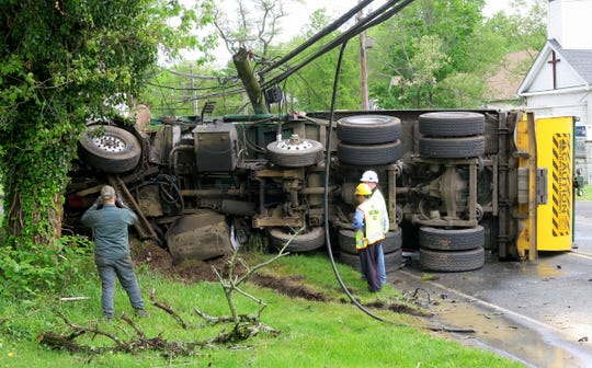 A Waste Management garbage truck overturned on West Farms Road at Casino Drive in Howell Township Tuesday morning, May 14, 2019.  At least two people were injured in the collison that spilled garbage on the roadway and cracked a utility pole.