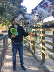 A city of Abilene photograph depicts Jesse Pottebaum, incoming director of the Abilene Zoo, feeding giraffes