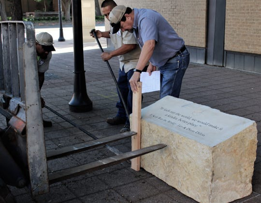 Richard Rogers, parks division manager for the city of Abilene, holds a piece of wood so skid of a forklift can adjust a 1,600-pound limestone bench without damaging it. The bench at the corner of Cypress and North Second streets was the first of 25 Art Adventure Trail pieces to be placed downtown.
