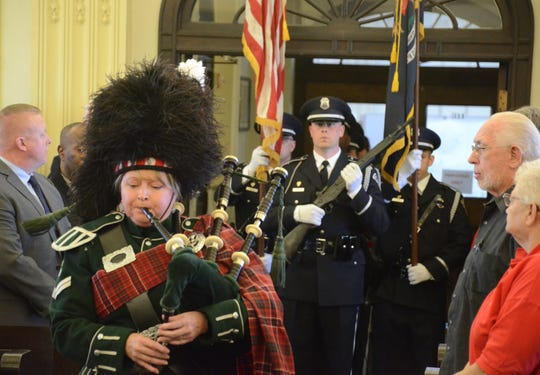 Bagpiper Michelle Brennan of Battle Creek leads the Battle Creek Police Department Honor Guard to begin the memorial service.