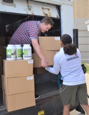 Jake Tindol, left, helps unload 870 boxes of protein powder that were donated to the Battle Creek Central athletic program.