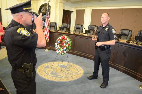 Officer Todd Rathjen photographs Sgt. Jeff Case holding the officer of the year trophy.