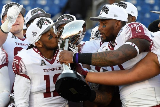 Temple Owls defensive back Kareem Ali (12)  kisses the American Athletic Conference football trophy during a post game celebration after defeating Navy Midshipmen 34-10 at Navy-Marine Corps Memorial Stadium in 2016.
