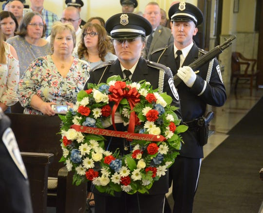 Officer Emily Leach carries the memorial wreath.