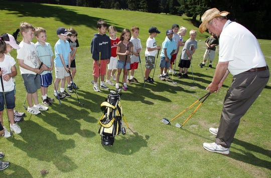 Club pro Ted Naff, right, displays different clubs for children at a summer camp at Gold Mountain.