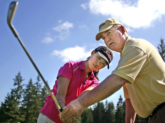 Ted Naff gives pointers to Erynne Lee in 2008, when the Silverdale junior player was emerging as one of the country's top women golfers. Lee is now in her second year on the LPGA Tour and Naff, who's been a swing coach to many of Kitsap's top players during his career at Golf Mountain Golf Club, is retiring.