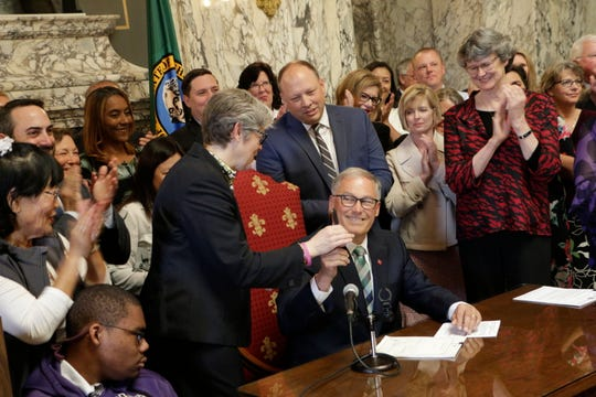 Gov. Jay Inslee, seated, hands Democratic Rep. Laurie Jinkins his pen after he signed a measure that makes Washington the first state in the nation to establish a program to help offset the costs of long-term care, Monday, May 13, 2019, in Olympia, Wash. Starting in 2025, the program promises a benefit for those who pay into the program, with a lifetime maximum of $36,500 per person, indexed to inflation, paid for by an employee payroll premium.