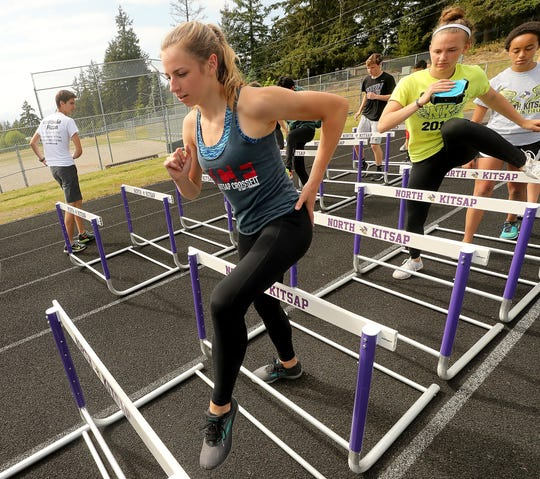 North Kitsap's Alyssa Cullen steps over a hurdle as she and fellow teammates run through drills during practice on Monday, May 13, 2019.
