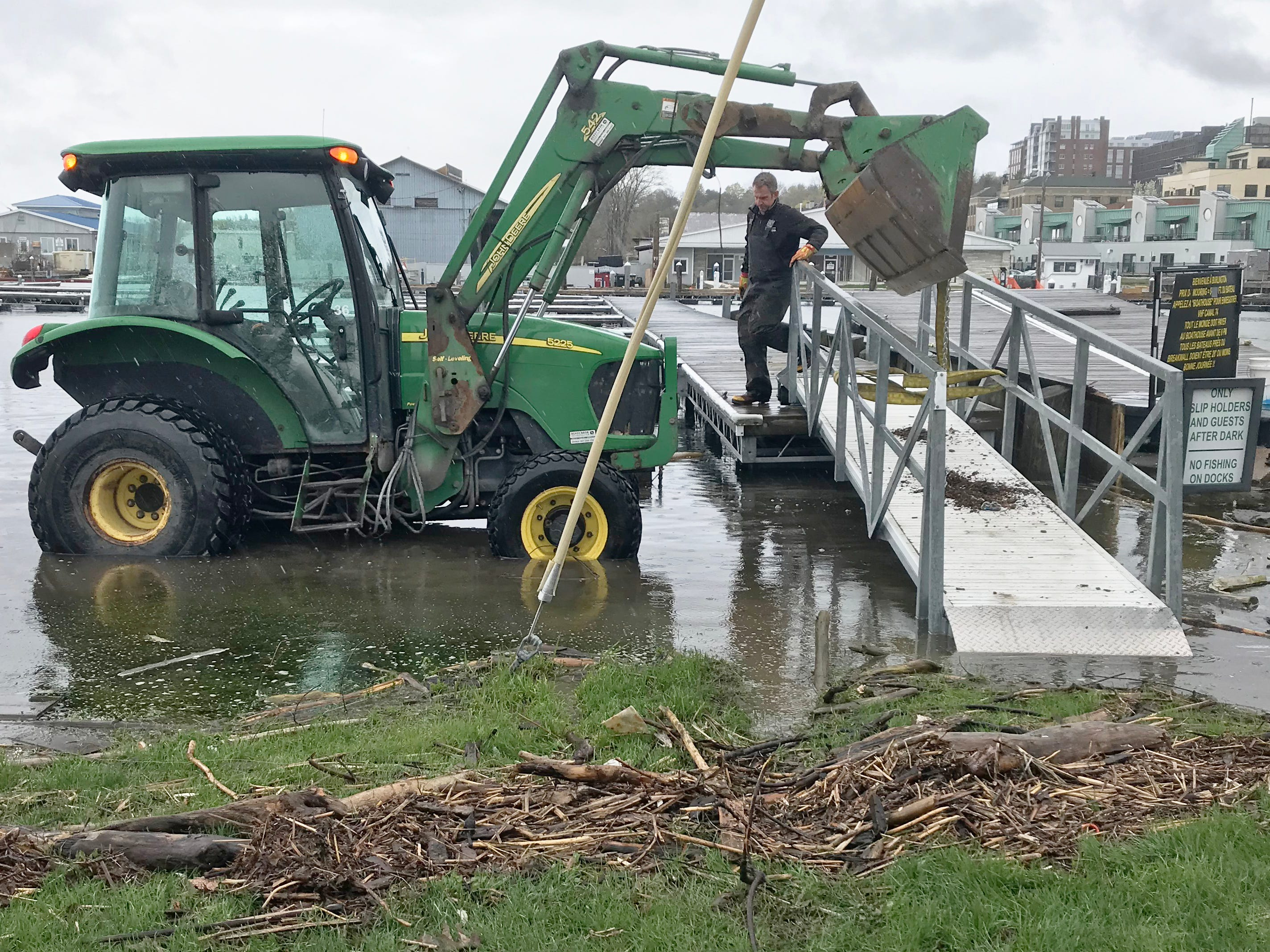 Kurt Hawkins, an event and marina specialist with Burlington Department of Parks, Recreation and Waterfront, steadies a gangway to floating docks at Perkins Pier on Tuesday, May 14, 2019. Lake Champlain is in its third week at flood stage.