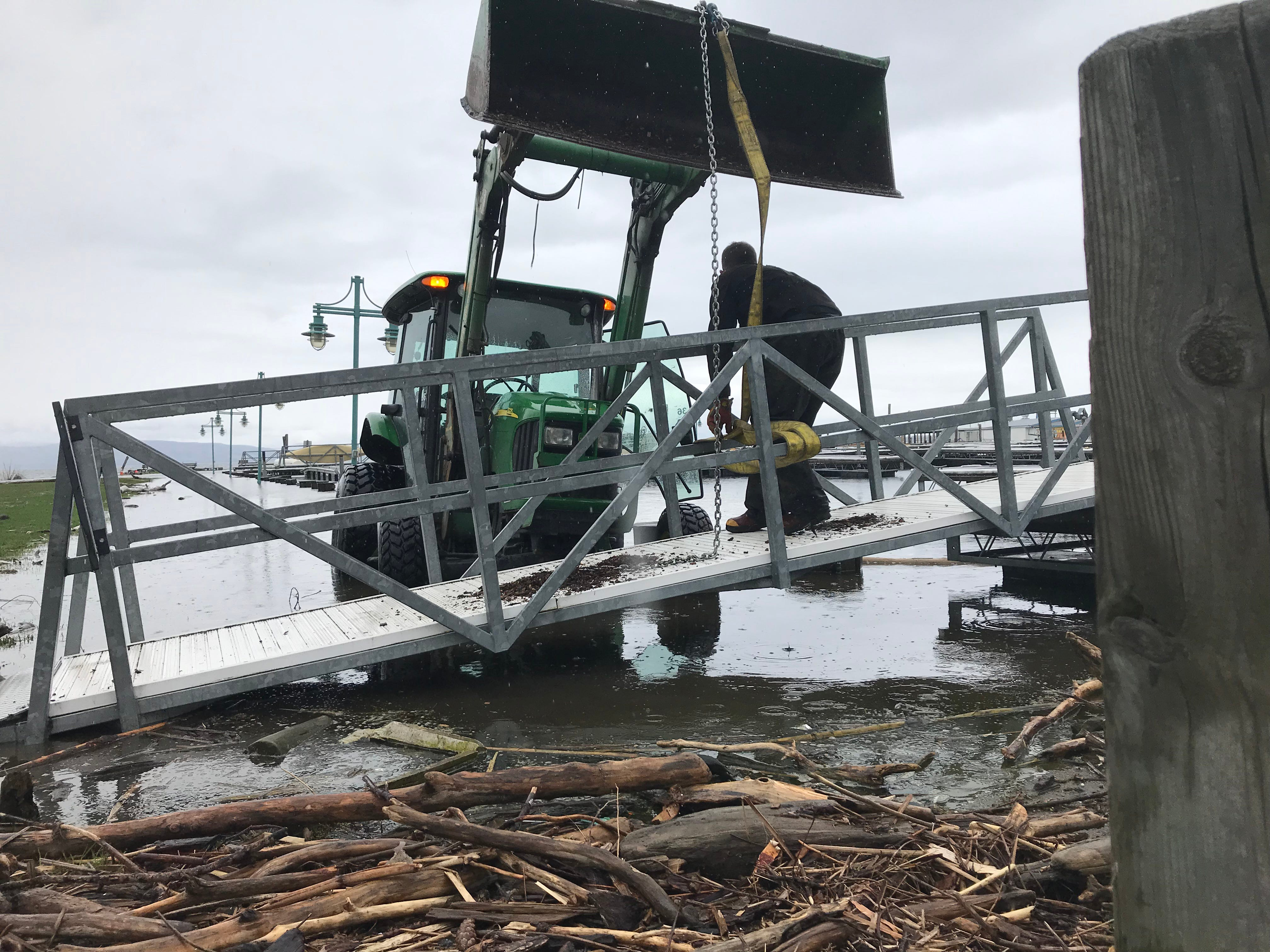 Kurt Hawkins, an event and marina specialist with Burlington Department of Parks, Recreation and Waterfront, maneuvers a gangway into position above floodwaters at Perkins Pier on Tuesday, May 14, 2019.
