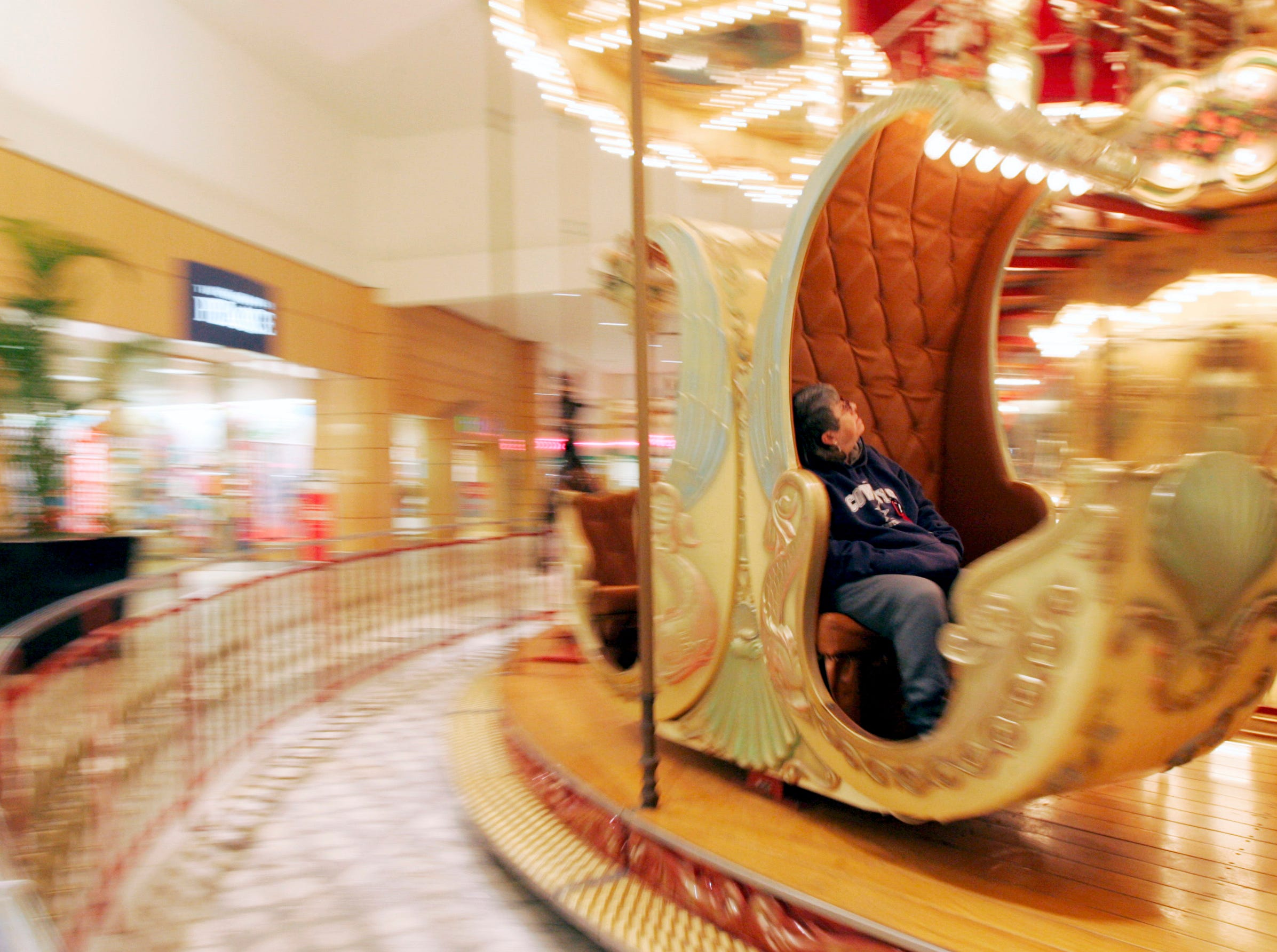 Ginger Bryant checks out the inside of her gondola seat Wednesday, Jan 14, 2009, as she rides the carousel at La Palmera mall in Corpus Christi.